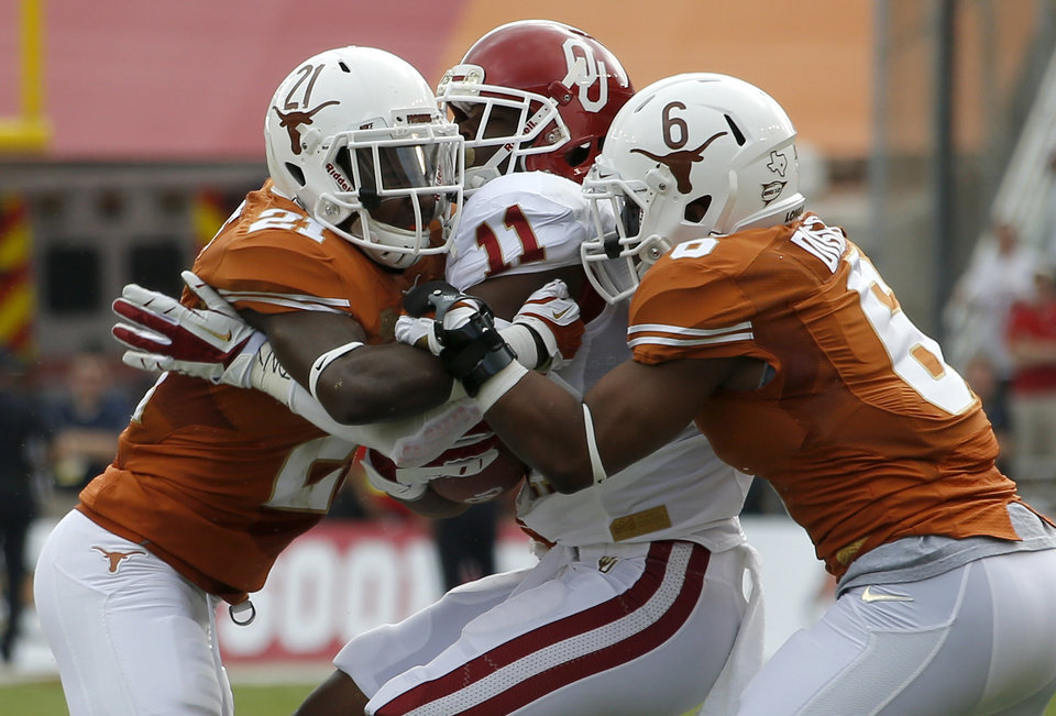 OU's Lacoltan Bester (11) is brought down by UT's Duke Thomas (21) and Aaron Benson (8) during the Red River Rivalry college football game between the University of Oklahoma Sooners and the University of Texas Longhorns at the Cotton Bowl Stadium in Dallas, Saturday, Oct. 12, 2013. Photo by Bryan Terry, The Oklahoman