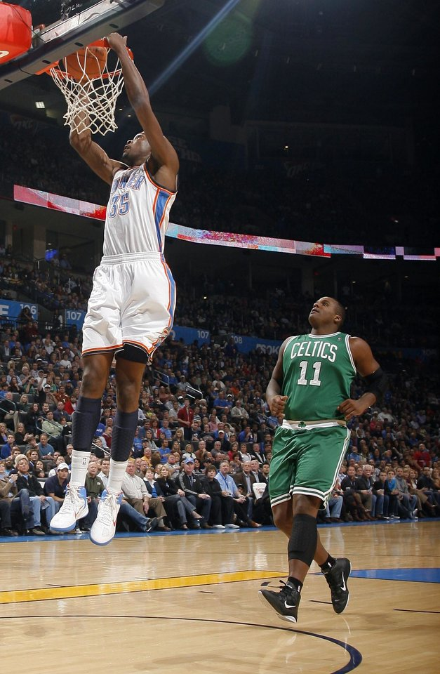 Photo - Oklahoma City's Kevin Durant (35) dunks in front of Boston's Glen Davis during the NBA game between the Oklahoma City Thunder and the Boston Celtics, Sunday, Nov. 7, 2010, at the Oklahoma City Arena. Photo by Sarah Phipps, The Oklahoman