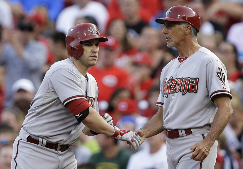 Photo - Arizona Diamondbacks' Miguel Montero, left, is congratulated by first base coach Dave McKay after Montero got a hit off Cincinnati Reds starting pitcher Homer Bailey to drive in a run in the fourth inning of a baseball game, Monday, July 28, 2014, in Cincinnati. (AP Photo/Al Behrman)