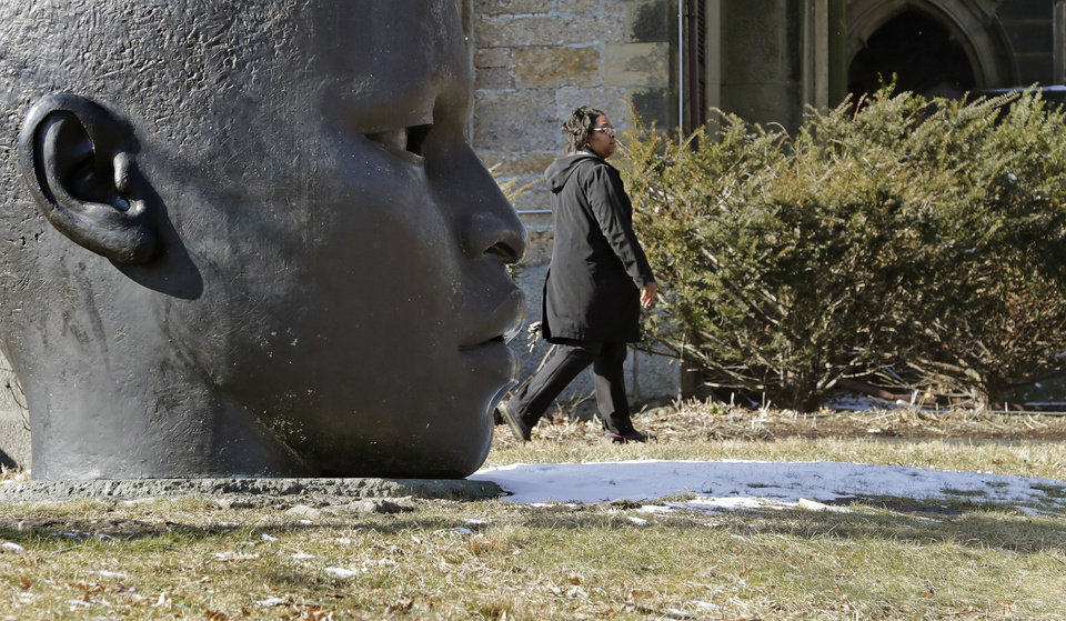 Photo - A woman walks on the partially snow-covered grass outside the National Center of Afro-American Artists in the Roxbury neighborhood of Boston, Wednesday, Feb. 6, 2013.  A midwinter storm headed to the Northeast on Friday could drop more than a foot of snow.  The sculpture at left is