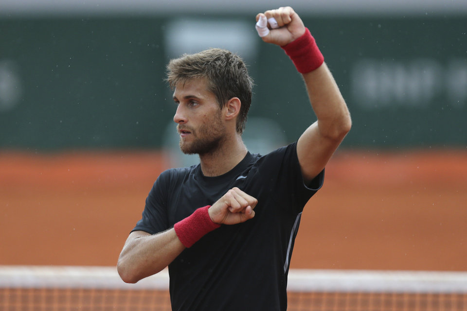 Photo - Slovakia's Martin Klizan celebrates defeating Japan's Kei Nishikori in three sets 7-6, 6-1, 6-2, in the first round match of the French Open tennis tournament at the Roland Garros stadium, in Paris, France, Monday, May 26, 2014. (AP Photo/David Vincent)
