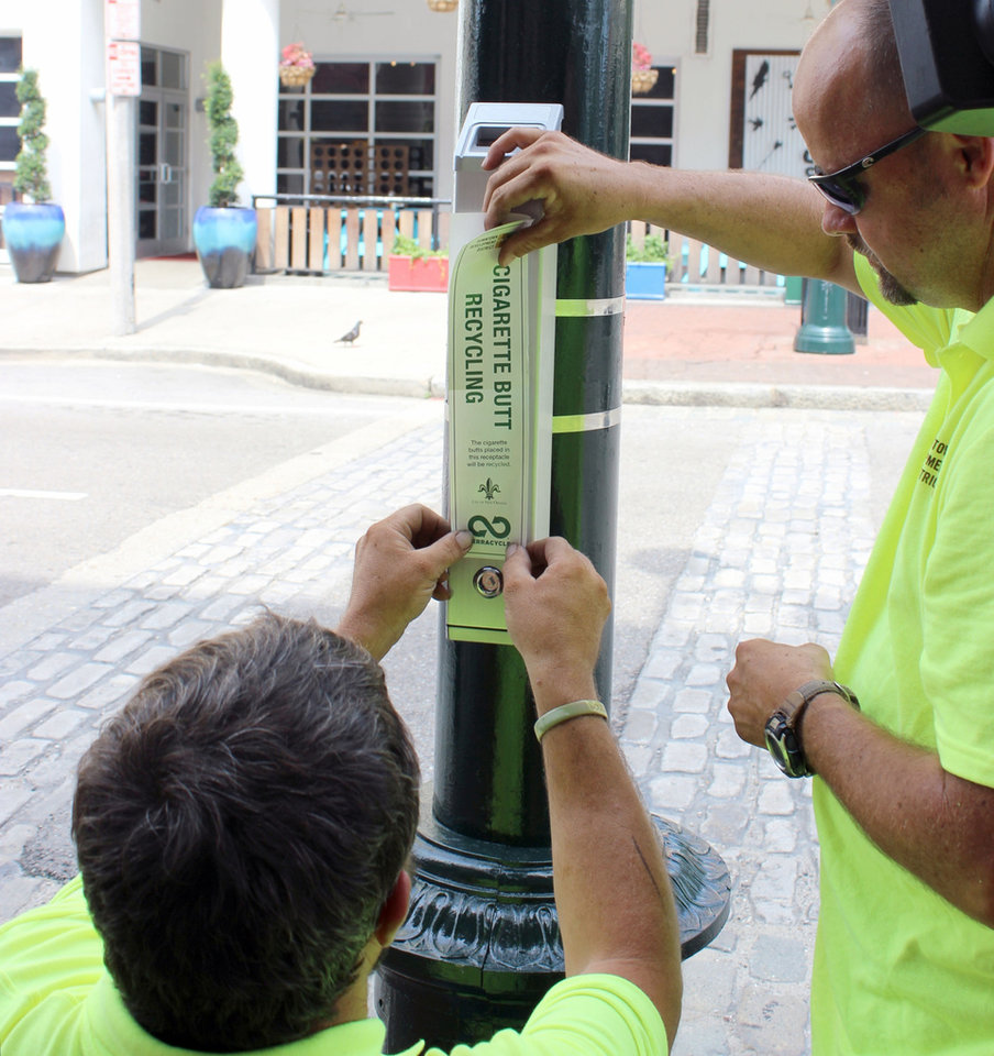Photo - Dale Alvin, right, and Jerry Howell apply a label, Monday, July 21, 2014,  to the first of about 50 cigarette butt recycling receptacles they will install in parts of New Orleans with heavy pedestrian traffic. TerraCycle Inc. says the Downtown Development District project is the first large-scale U.S. entry in a cigarette recycling project that started in Canada. (AP Photo/Janet McConnaughey)