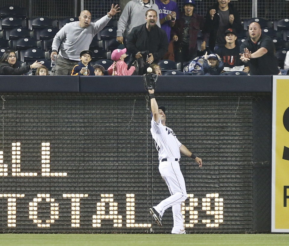 Photo - San Diego Padres left fielder Seth Smith reaches back to make the running catch at the wall on a drive hit by Colorado Rockies' Justin Morneau in the fifth inning of a baseball game Monday, April 14, 2014, in San Diego. (AP Photo/Lenny Ignelzi)