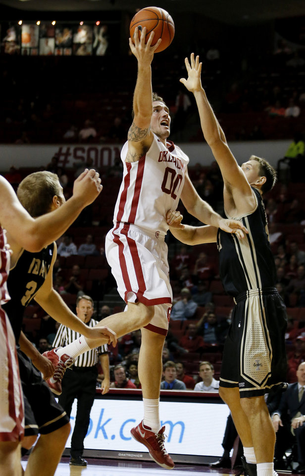 Photo - Oklahoma's Ryan Spangler (00) puts up a shot over Idaho's Joe Kammerer (42) during a college basketball game between the University of Oklahoma Sooners and the Idaho Vandals at Lloyd Noble Center in Norman, Okla., on Wednesday, Nov. 13, 2013. Wednesday, Nov. 13, 2013. Photo by Bryan Terry, The Oklahoman
