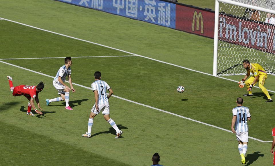 Photo - Argentina's goalkeeper Sergio Romero. right, blocks the ball after a header from Iran's Reza Ghoochannejhad during the group F World Cup soccer match between Argentina and Iran at the Mineirao Stadium in Belo Horizonte, Brazil, Saturday, June 21, 2014. (AP Photo/Sergei Grits)