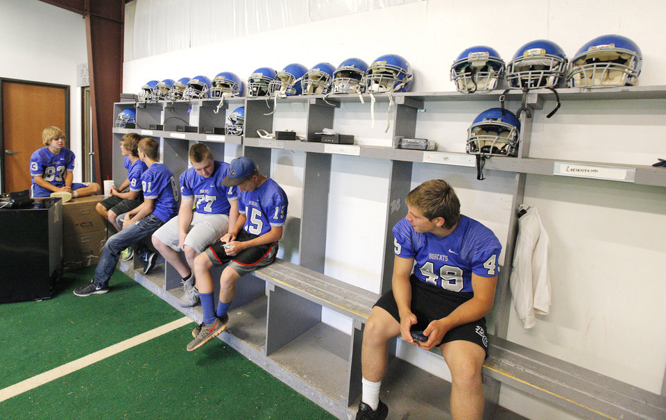 Photo - At far right freshman linebacker Bailey Chase, age 15, looks over at teammates as they sit under the few remaining football helmets in the field house at Bridge Creek High School in Bridge Creek Monday, Aug. 11, 2014.  Vandals spread paint, carpet glue, and rat poison on football equipment and furniture throughout the building. Carpets had to be removed and many items placed in the trash leaving Bridge Creek without enough helmets, jerseys and other equipment .  Photo by Paul B. Southerland, The Oklahoman