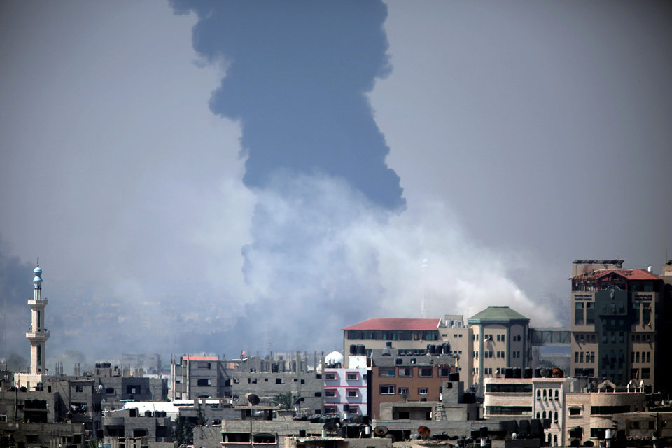 Photo - Smoke rises from an Israeli strike at a building in Gaza City, foreground, as black smoke billows from Gaza's electricity distribution company, background, after it was hit earlier by Israeli strikes in the Nusayrat refugee camp, central Gaza Strip, Tuesday, July 29, 2014.  Israel struck symbols of Hamas' control of Gaza and the strip's only power plant on Tuesday, escalating its military campaign against the Islamic militant group with the heaviest bombardment in the fighting so far.(AP Photo/Khalil Hamra)