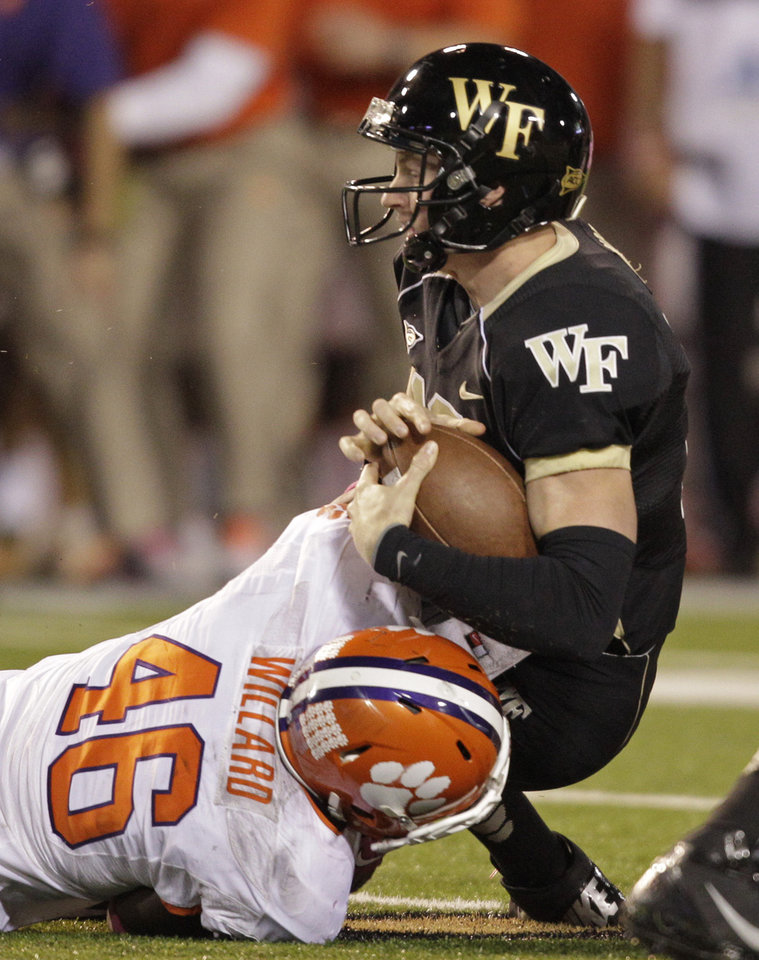 Photo -   Wake Forest's Tanner Price, right, is sacked by Clemson's Jonathan Willard, left, during the first half of an NCAA college football game in Winston-Salem, N.C., Thursday, Oct. 25, 2012. (AP Photo/Chuck Burton)