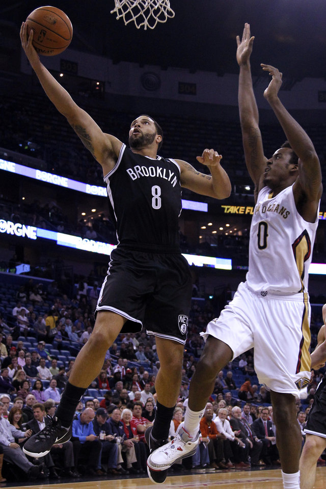 Photo - Brooklyn Nets guard Deron Williams (8) drives past New Orleans Pelicans forward Al-Farouq Aminu (0) during the first half of an NBA basketball game in New Orleans, Monday, March 24, 2014. (AP Photo/Jonathan Bachman)