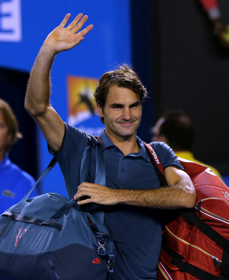 Photo - Roger Federer of Switzerland waves after defeating Andy Murray of Britain in their quarterfinal at the Australian Open tennis championship in Melbourne, Australia, Wednesday, Jan. 22, 2014. (AP Photo/Aaron Favila)