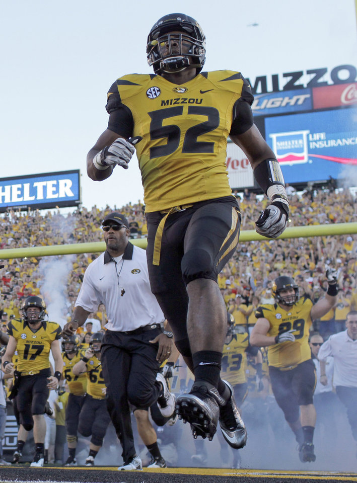 Photo - FILE - In this Sept. 8, 2012 file photo, Missouri's Michael Sam (52) runs onto the field along with their teammates before the start of an NCAA college football game against Georgia in Columbia, Mo. Michael Sam hopes his ability is all that matters, not his sexual orientation.  Missouri's All-America defensive end came out to the entire country Sunday night, Feb. 9, 2014, and could become the first openly gay player in America's most popular sport. (AP Photo/Jeff Roberson, File)