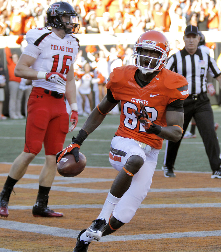 Oklahoma State\'s Isaiah Anderson (82) reacts after a touchdown in front of Texas Tech\'s Cody Davis (16) during the college football game between the Oklahoma State University Cowboys (OSU) and Texas Tech University Red Raiders (TTU) at Boone Pickens Stadium on Saturday, Nov. 17, 2012, in Stillwater, Okla. Photo by Chris Landsberger, The Oklahoman