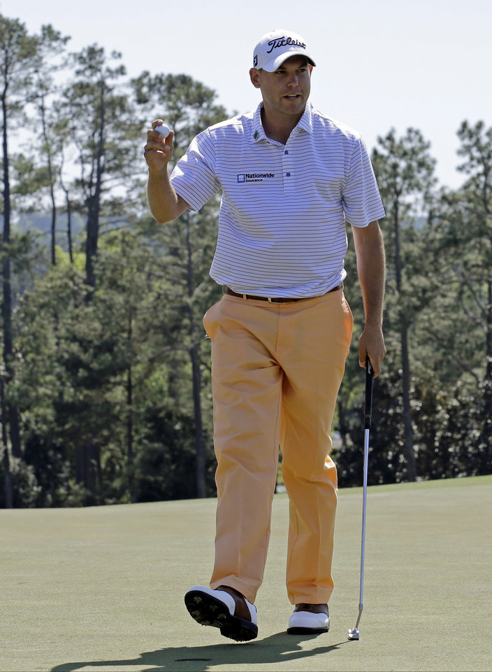 Photo - Bill Haas holds up his ball after a birdie putt on the 18th hole during the first round of the Masters golf tournament Thursday, April 10, 2014, in Augusta, Ga. (AP Photo/David J. Phillip)