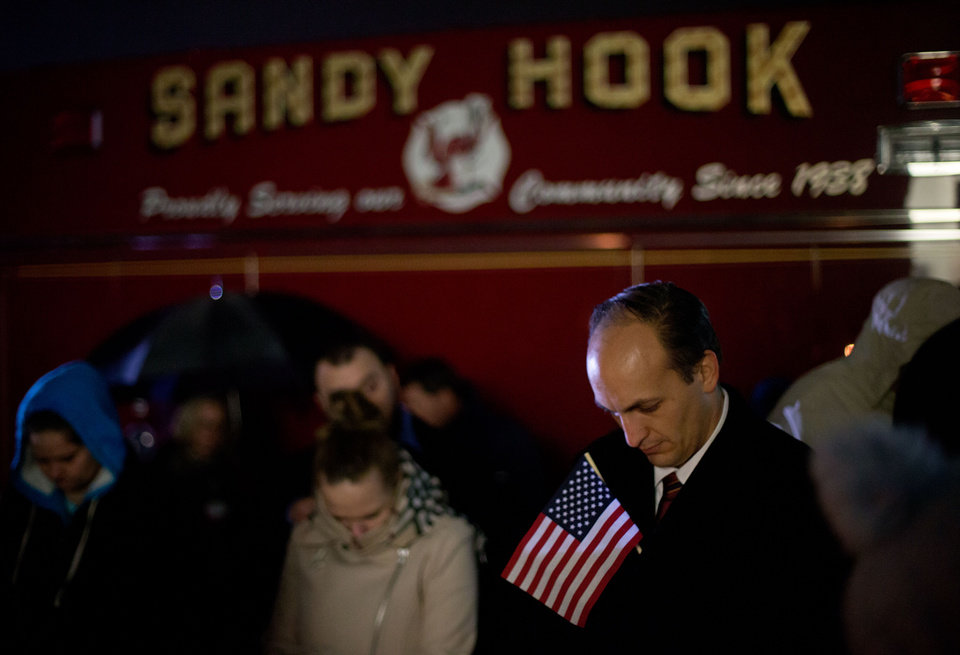 Mourners listen to a memorial service over a loudspeaker outside Newtown High School for the victims of the Sandy Hook Elementary School shooting, Sunday, Dec. 16, 2012, in Newtown, Conn. (AP Photo/David Goldman)
