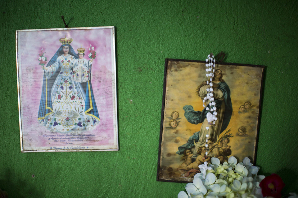 Photo - Two images of the virgin Mary and a rosary hang on a wall at the Ramos Juarez's home in the community of San Jose Las Flores, in the northern Cuchumatanes mountains of Guatemala, Tuesday, July 1, 2014. In this small community Gilberto Francisco Ramos Juarez was born, a Guatemalan boy whose decomposed body was found in the Rio Grande Valley of South Texas. The border patrol had found Gilberto Francisco's decaying body in the Texas desert near the border. He was shirtless, probably having died of heat stroke, and still wearing a white rosary. (AP Photo/Luis Soto)
