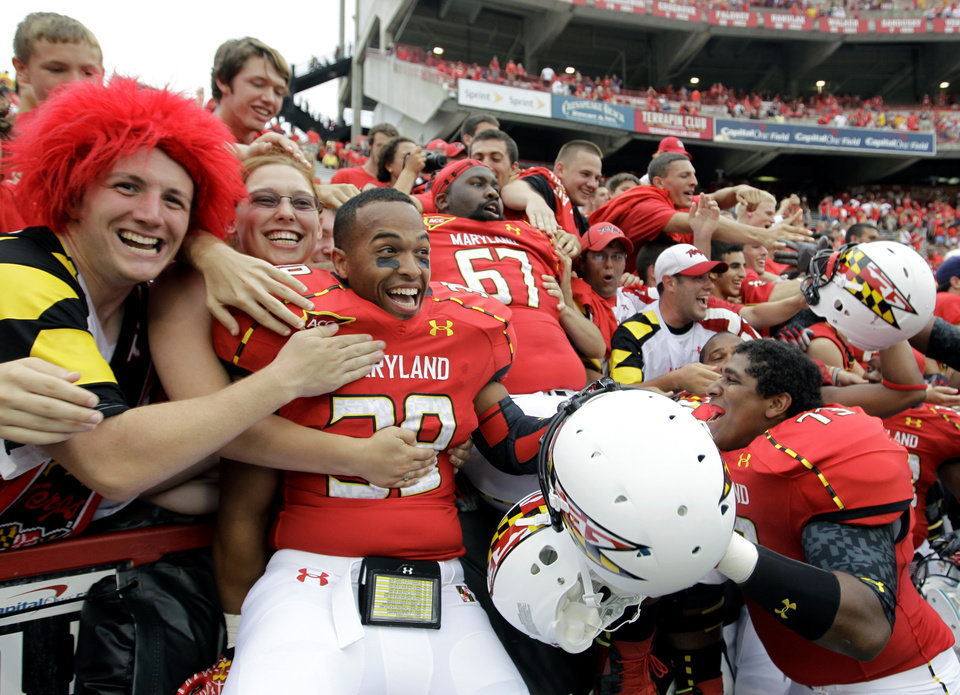 Photo -   Maryland's Jeff Hernandez, center left, Peter White (67) and Alex Walker, lower right, celebrate with fans after defeating William & Mary 7-6 in an NCAA college football game, Saturday, Sept. 1, 2012, in College Park, Md. (AP Photo/Luis M. Alvarez)