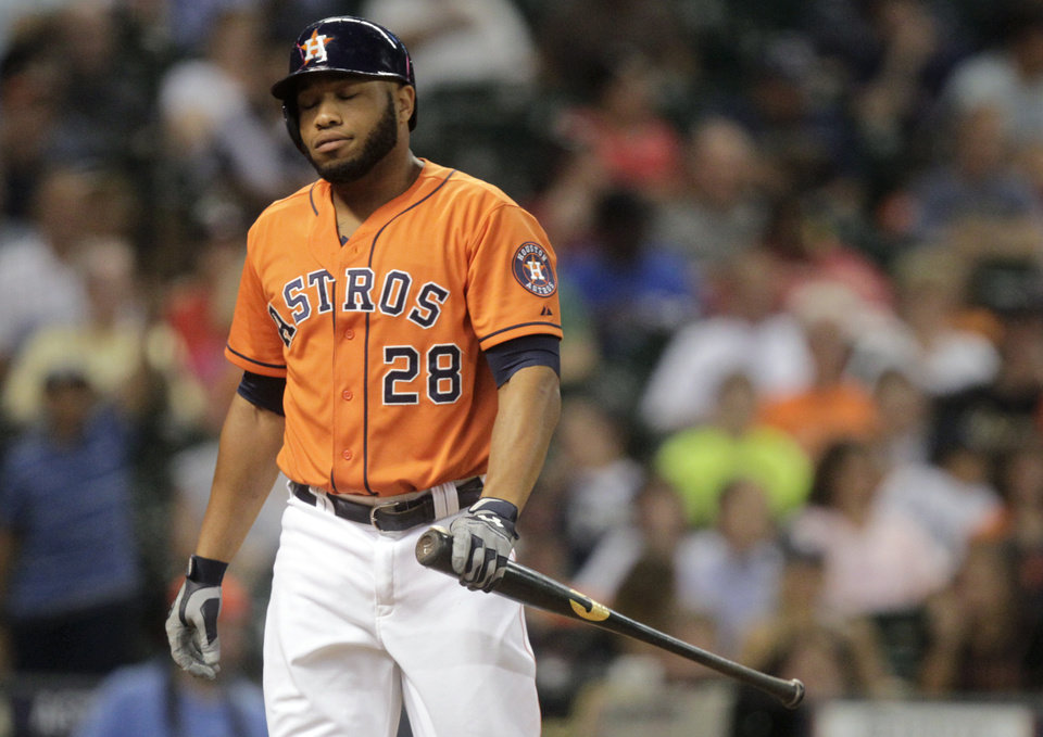 Photo - Houston Astros' Jon Singleton walks back to the dugout after striking out to end the eighth inning stranding teammate Jason Castro at second during a baseball game against the Miami Marlins, Friday, July 25, 2014, in Houston. (AP Photo/Patric Schneider)
