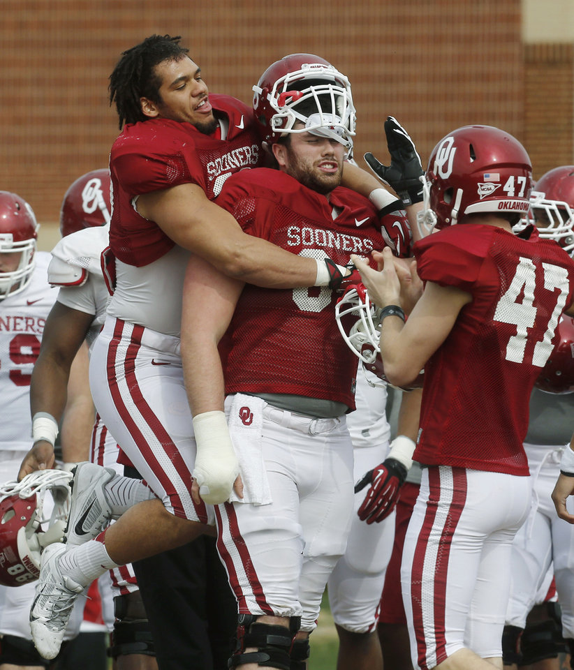 Oklahoma's Trey Millard, left, jokes around with lineman Gabe Ikard, center, during spring practice for the NCAA college football team in Norman, Okla., Tuesday, March 12, 2013. Eric Hosek is at right. (AP Photo/Sue Ogrocki) ORG XMIT: OKSO104
