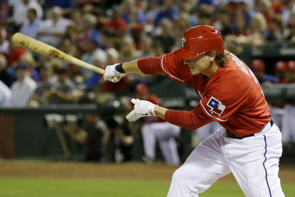 Photo - Texas Rangers' Jim Adduci swings and strikes out against Pittsburgh Pirates' Gerrit Cole in the fifth inning of a baseball game, Monday, Sept. 9, 2013, in Arlington, Texas. Adduci suffered an unknown injury in the at-bat and left the game. (AP Photo/Tony Gutierrez)