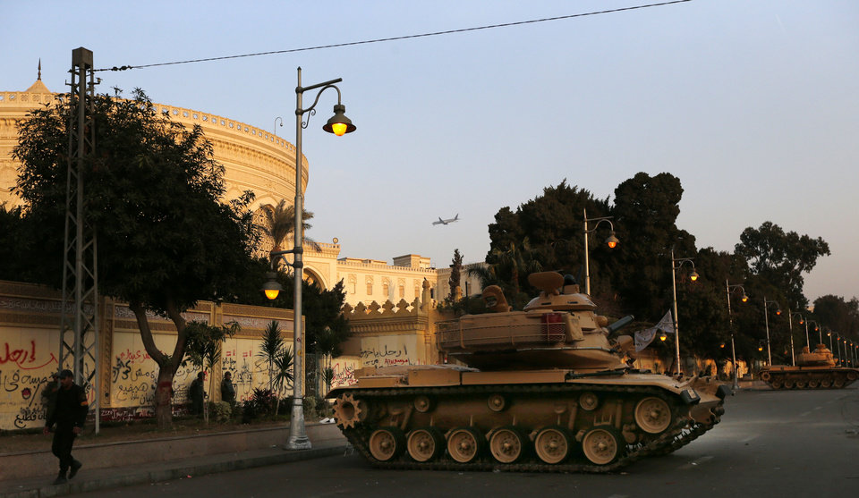 """Military tanks guard, as a plane files past the presidential palace in Cairo, Egypt, Sunday, Dec. 16, 2012. Key Egyptian rights groups called Sunday for a repeat of the first round of the constitutional referendum, alleging the vote was marred by widespread violations. Islamists who back the disputed charter claimed they were in the lead with a majority of """"yes"""" votes. (AP Photo/Petr David Josek)"""