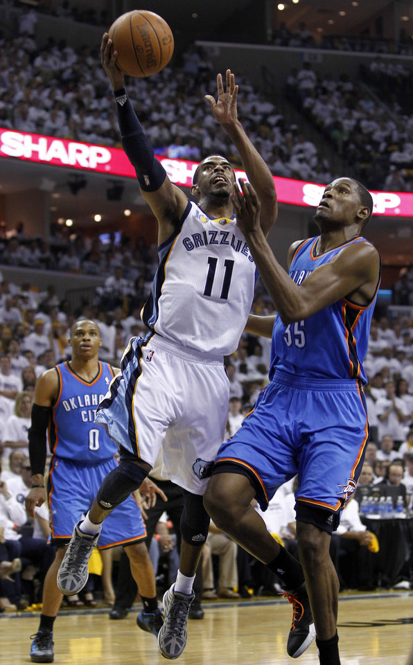 Photo - Memphis Grizzlies guard Mike Conley (11) shoots against Oklahoma City Thunder forward Kevin Durant (35) during the first half of Game 4 of a second-round NBA basketball playoff series on Monday, May 9, 2011, in Memphis, Tenn. At left is Thunder guard Russell Westbrook (0). (AP Photo/Wade Payne)
