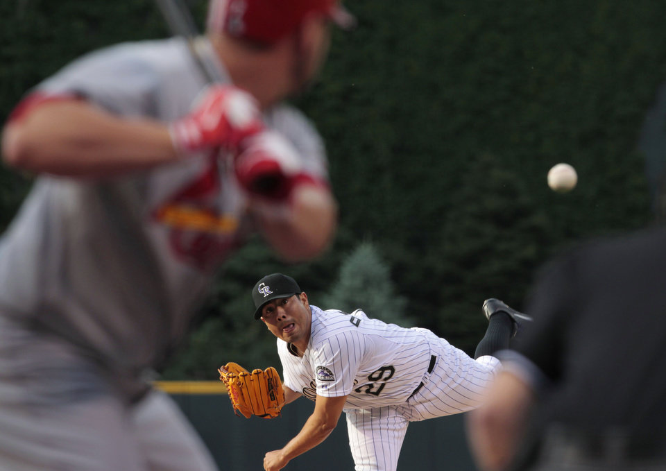 Photo - Colorado Rockies starter Jorge De La Rosa (29) pitches to St. Louis Cardinals' Matt Holliday in the first inning of a baseball game in Denver on Tuesday, June 24, 2014. (AP Photo/Joe Mahoney)