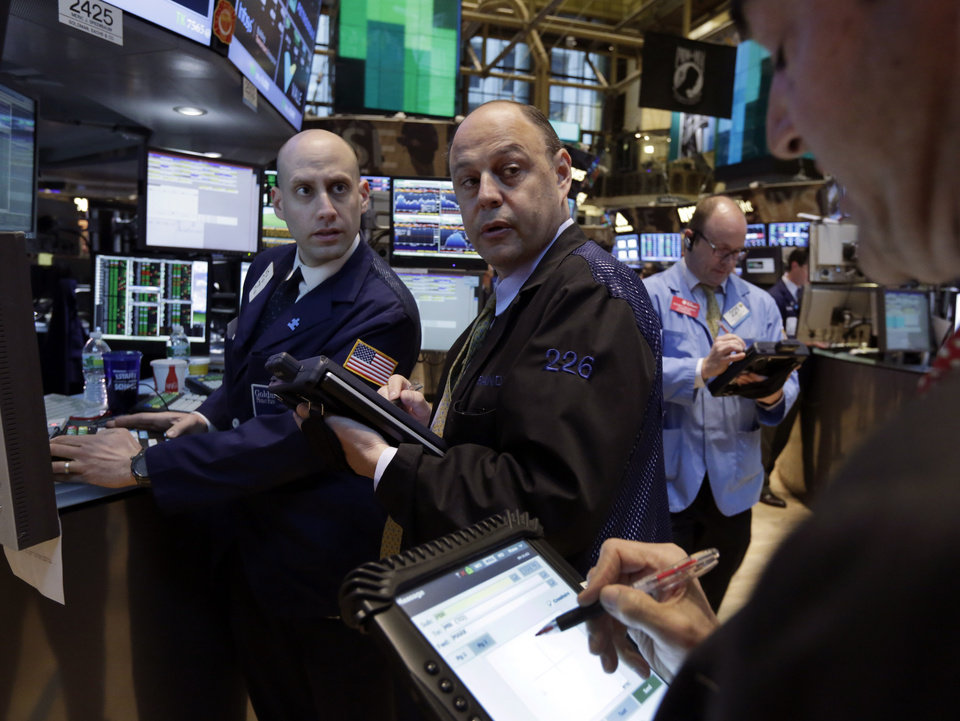 Photo - Specialist Meric Greenbaum, left, works with traders on the floor of the New York Stock Exchange Monday, April 29, 2013.  A pair of encouraging economic reports helped propel the stock market up in early trading on Monday. (AP Photo/Richard Drew)