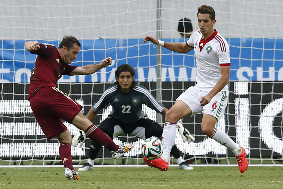Photo - Russia's Alexander Kerzhakov, left, shoots as Morocco's Zouhair Feddal, right, tries to block during a friendly soccer match in Moscow, Russia, Friday, June 6, 2014. Russia won 2-0. This is the last friendly match before the Russian team leaves for Brazil to compete in the World Cup. (AP Photo/\Name\)
