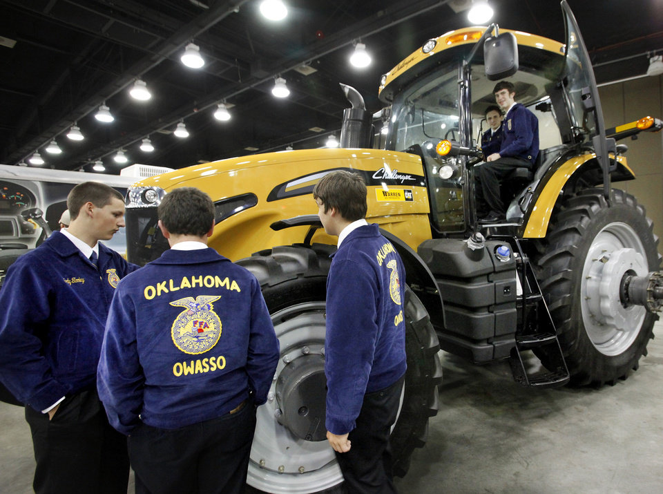 Photo - Convention attendees check out a CAT Challenger tractor on display Tuesday as part of the trade show during the annual state convention of FFA members at the Cox Convention Center in Oklahoma City. Photo by Jim Beckel, The Oklahoman