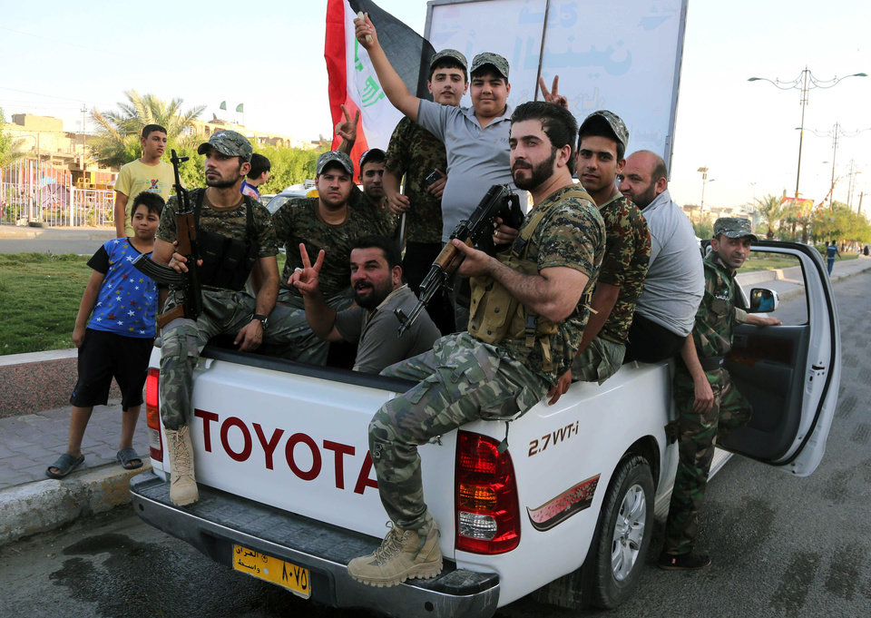Photo - Iraqi Shiite tribal fighters wearing military uniforms chant slogans against the al-Qaida-inspired Islamic State of Iraq and the Levant in Baghdad's Sadr city, Iraq, Tuesday, June 17, 2014, after authorities urged Iraqis to help battle insurgents. Thousands of Shiites from Baghdad and across southern Iraq answered an urgent call to arms Saturday, joining security forces to fight the Islamic militants who have captured large swaths of territory north of the capital and now imperil a city with a much-revered religious shrine. (AP Photo/Karim Kadim)
