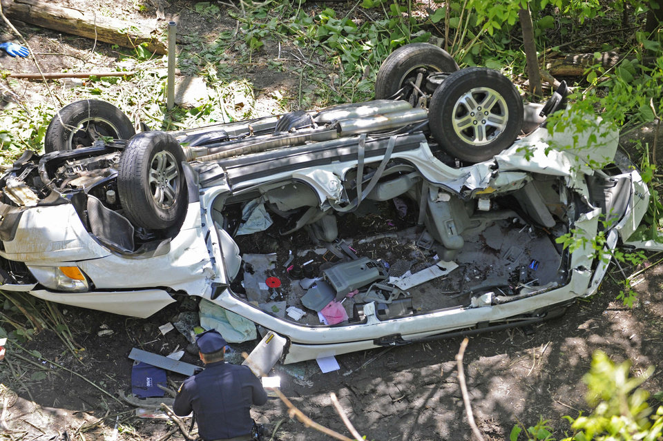 Photo -   Police investigate the destroyed van that plunged over the Bronx River Parkway, Sunday April 29, 2012, in New York. Authorities say the out-of-control van plunged off a roadway near the Bronx Zoo, killing seven people, including three children. (AP Photo/ Louis Lanzano)