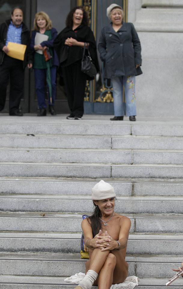 Photo -   A naked protester sits on the steps of City Hall in San Francisco, Tuesday, Nov. 20, 2012. San Francisco lawmakers on Tuesday narrowly approved a proposal to ban public nakedness, rejecting arguments that the measure would eat away at a reputation for tolerance enjoyed by a city known for flouting convention and flaunting its counter-culture image. The 6-5 Board of Supervisors vote means that exposed genitals will be prohibited in most public places, including streets, sidewalks and public transit. (AP Photo/Jeff Chiu)