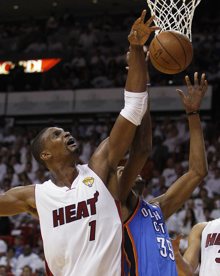 Miami Heat power forward Chris Bosh (1) and Oklahoma City Thunder small forward Kevin Durant (35) go for a rebound during the second half at Game 3 of the NBA Finals basketball series, Sunday, June 17, 2012, in Miami. (AP Photo/Lynne Sladky) ORG XMIT: NBA136