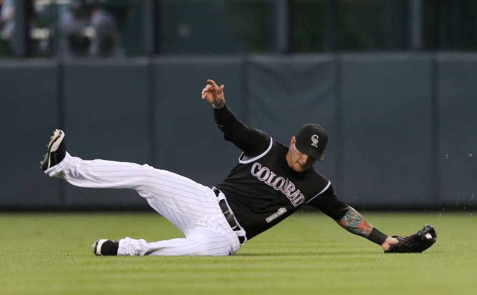 Photo - Colorado Rockies rightfielder Brandon Barnes pulls in fly ball off the bat of Miami Marlins' Casey McGehee in the fifth inning of a baseball game in Denver on Saturday, Aug. 23, 2014. (AP Photo/David Zalubowski)