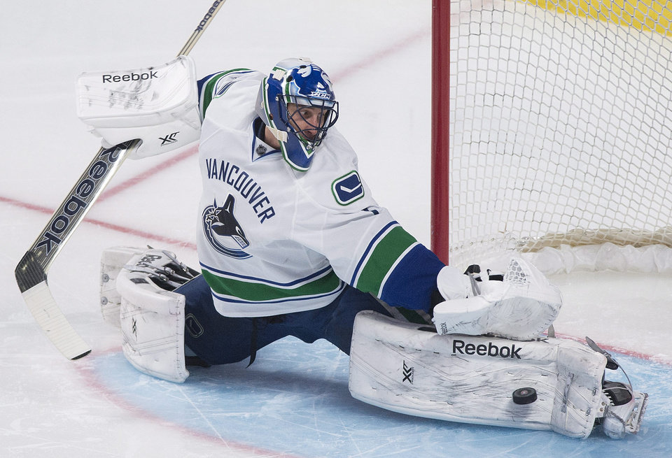 Photo - Vancouver Canucks goaltender Roberto Luongo makes a save against the Montreal Canadiens during the second period of an NHL hockey game Thursday, Feb. 6, 2014, in Montreal. (AP Photo/The Canadian Press, Graham Hughes)