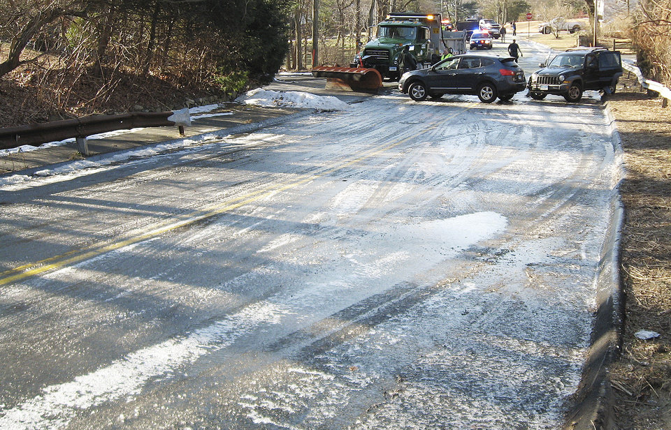 Photo - In this Thursday, Jan. 9, 2014 photo, released by the Norwalk Police Department, a sheet of ice covers Flax Hill Road in Norwalk, Conn. Alfredo Bahena-Benitez, a pool company worker, was arrested on charges that he drained a swimming pool in freezing temperatures onto the road, causing several car crashes. (AP Photo/Norwalk Police Department)