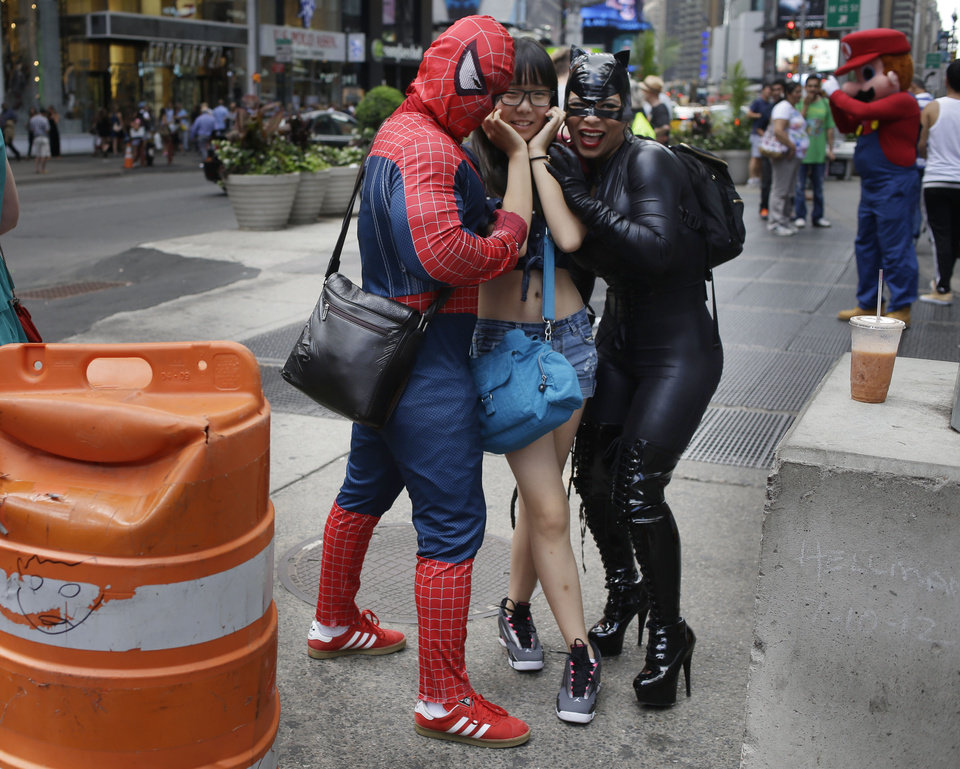 "Photo - People dressed as Catwoman, right, and Spiderman, left, take a picture with a tourist in Times Square on Monday, July 28, 2014 in New York. New York City Mayor Bill de Blasio said Monday that he believes the people wearing character costumes in Times Square should be licensed and regulated. Dozens of people dressed as kids' favorites like Elmo, Cookie Monster and Batman stand near 42nd Street and pose for photos with tourists in exchange for money. De Blasio said the practice has ""gone too far.""  A man dressed as Spider-man was arrested Saturday, July 28, 2014, after punching a police officer who told him to stop harassing tourists.  The City Council is working on legislation that would require the characters to get a city-approved license.  (AP Photo/Seth Wenig)"