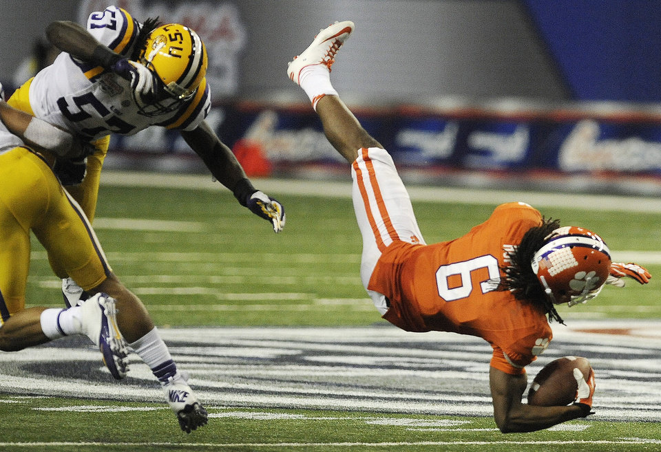 Photo - Clemson wide receiver DeAndre Hopkins (6) makes a catch as LSU linebacker Lamin Barrow (57) defends during the second half of the Chick-fil-A Bowl NCAA college football game, Monday, Dec. 31, 2012, in Atlanta. Barrow was injured on the play. (AP Photo/Mike Stewart)