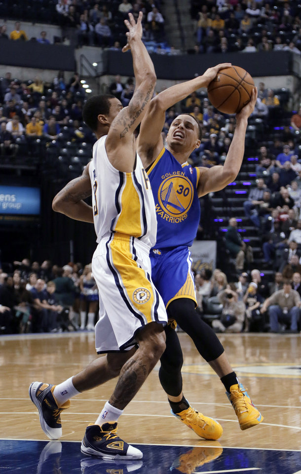 Golden State Warriors guard Stephen Curry, right, drives in front of Indiana Pacers guard George Hill during the first half of an NBA basketball game in Indianapolis, Tuesday, Feb. 26, 2013. (AP Photo/AJ Mast)
