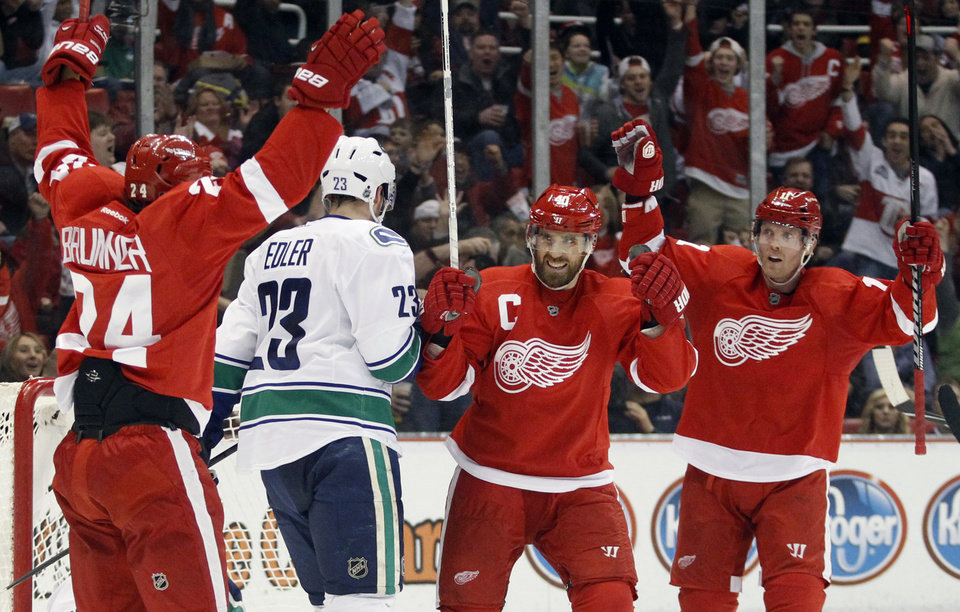 Detroit Red Wings center Henrik Zetterberg, second from right, of Sweden, celebrates his goal with right wing Daniel Cleary, right, and center Damien Brunner (24) as Vancouver Canucks defenseman Alexander Edler (23), of Sweden, skates away in the second period of an NHL hockey game Sunday, Feb. 24, 2013, in Detroit. (AP Photo/Duane Burleson)