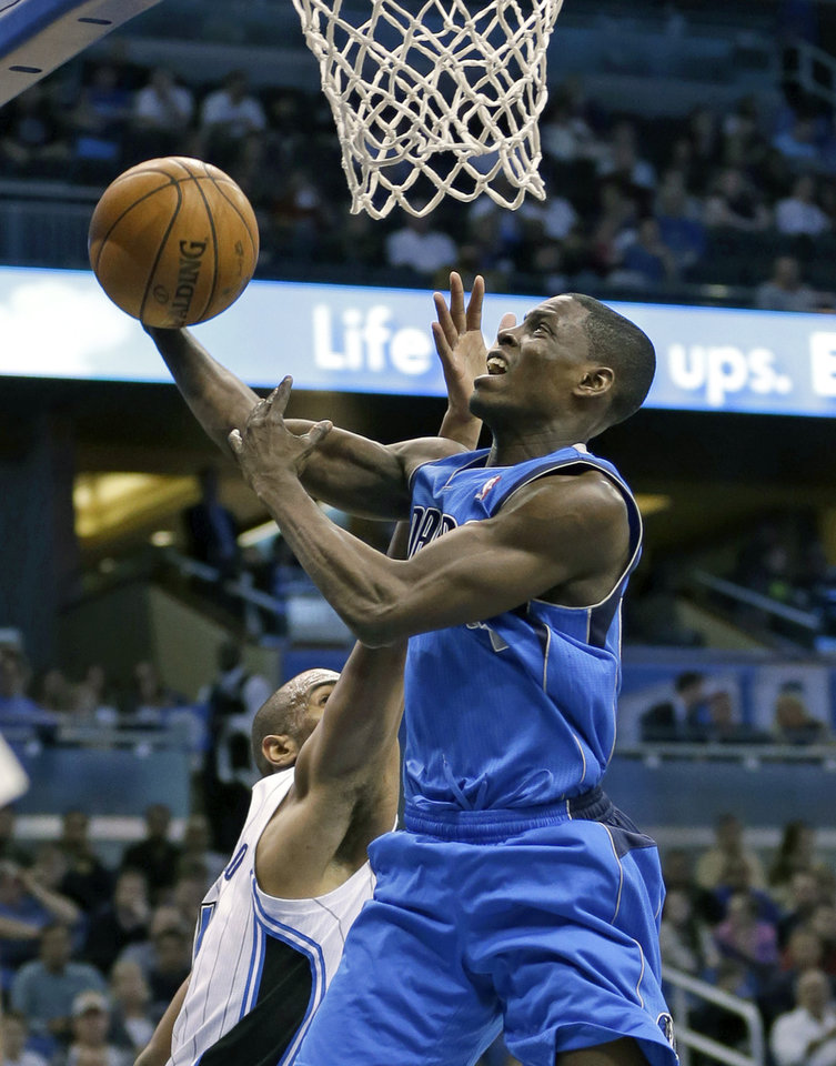 Dallas Mavericks' Darren Collison, right, drives to the basket past Orlando Magic's Arron Afflalo, left, during the first half of an NBA basketball game, Sunday, Jan. 20, 2013, in Orlando, Fla. (AP Photo/John Raoux)