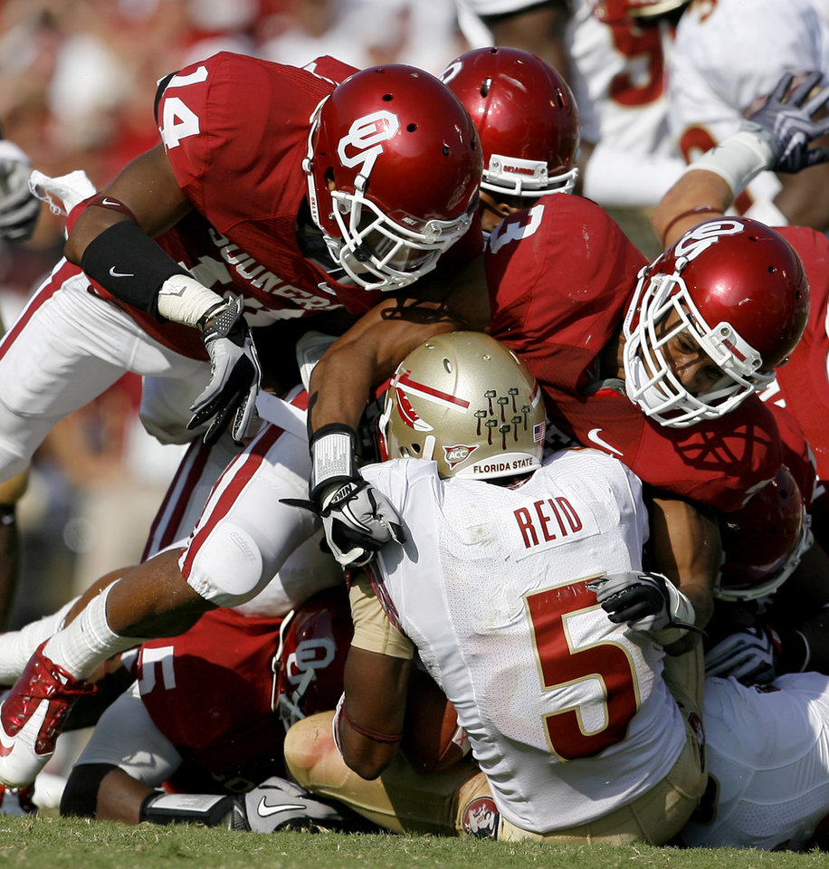 Photo - OU's Aaron Colvin, left, and Jonathan Nelson bring down Florida State's Greg Reid during the second half of the college football game between the University of Oklahoma Sooners (OU) and Florida State University Seminoles (FSU) at the Gaylord Family-Oklahoma Memorial Stadium on Saturday, Sept. 11, 2010, in Norman, Okla.   Photo by Bryan Terry, The Oklahoman