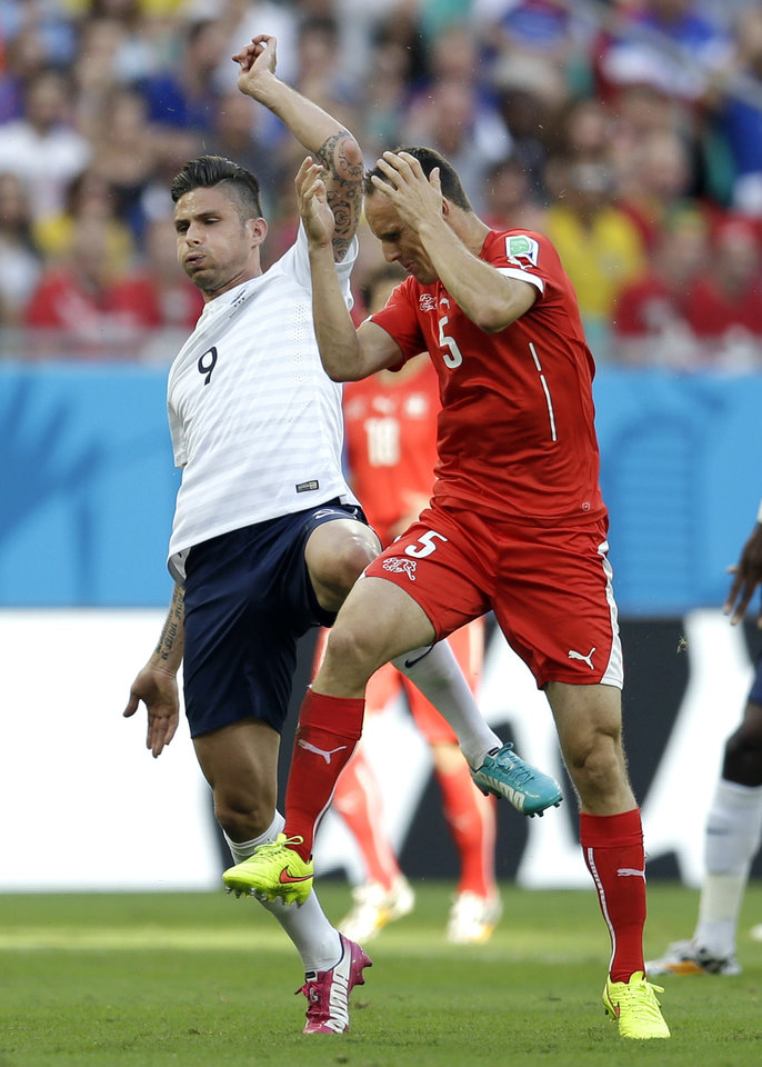 Photo - Switzerland's Steve von Bergen reacts after getting hit by France's Olivier Giroud during the group E World Cup soccer match between Switzerland and France at the Arena Fonte Nova in Salvador, Brazil, Friday, June 20, 2014. (AP Photo/Natacha Pisarenko)