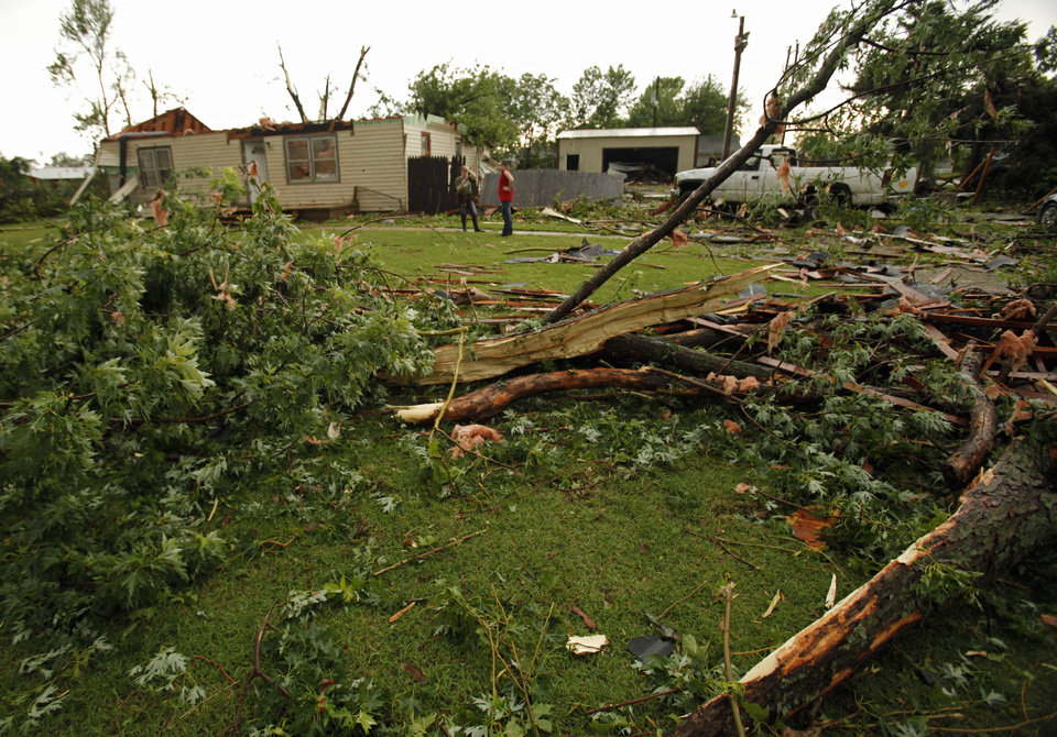 Photo - April Stout and her step-daughter Tiffany survey damage to their rented home after a tornado-spawning storm swept through the state on Tuesday, May 24, 2011, in Newcastle, Okla. Photo by Steve Sisney, The Oklahoman ORG XMIT: KOD