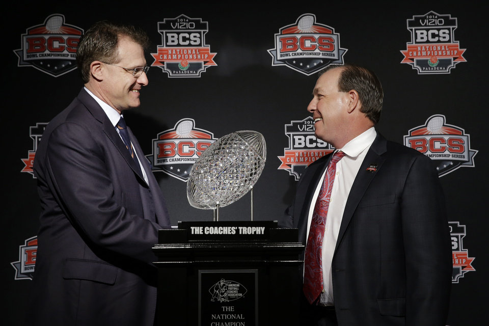 Photo - Auburn head coach Gus Malzahn, left, and Florida State head coach Jimbo Fisher shake hands in front of The Coaches' Trophy during a news conference for the NCAA BCS National Championship college football game Sunday, Jan. 5, 2014, in Newport Beach, Calif. Florida State plays Auburn on Monday, Jan. 6, 2014. (AP Photo/David J. Phillip)