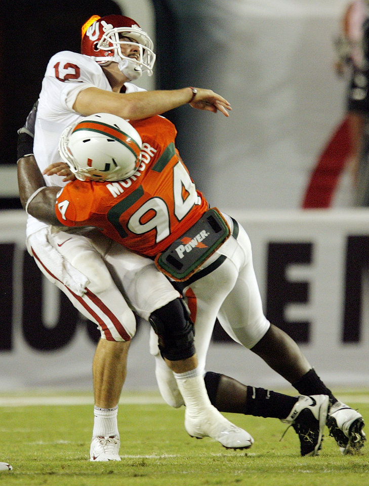 Photo - OU quarterback Landry Jones (12) is hit after making a throw by Miami's Eric Moncur (94) during the college football game between the University of Oklahoma (OU) Sooners and the University of Miami (UM) Hurricanes at Land Shark Stadium in Miami Gardens, Florida, Saturday, October 3, 2009. Miami won, 21-20. The pass fell incomplete. Photo by Nate Billings, The Oklahoman