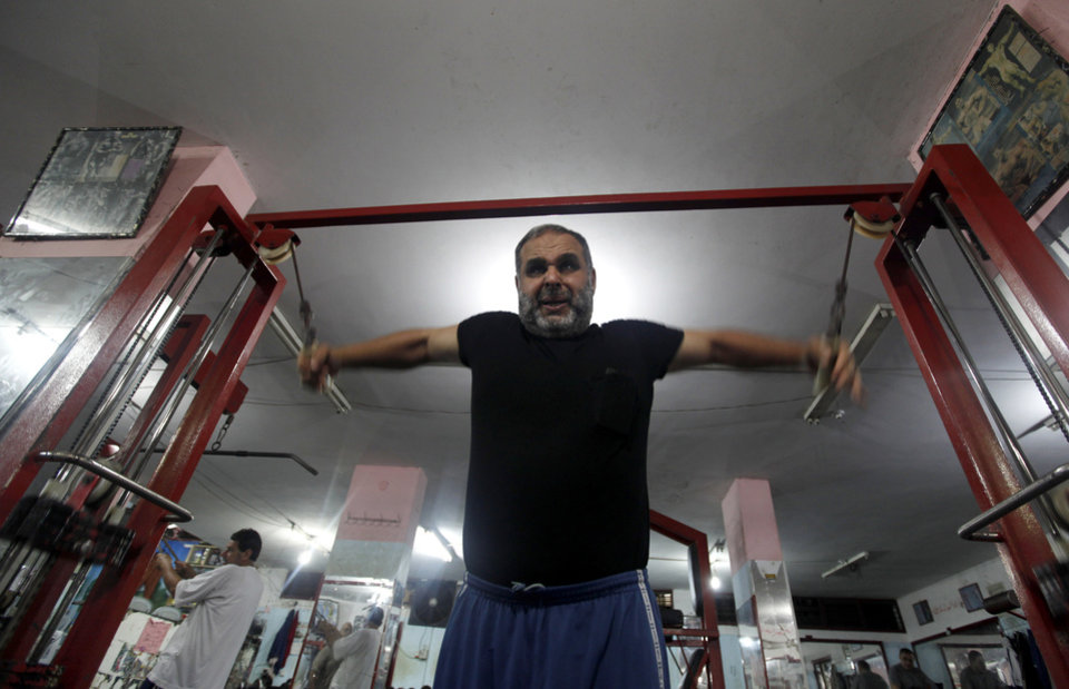 Photo - In this Monday, June 24, 2013 photo, Mohammed Rantisi, 55, does exercises early morning at al-Nasser Gym in Gaza City. On the day of his induction, Baraa, Mohammed's son, was told to wait near a mosque. A white car drove up. Secret passwords were exchanged. And then he was sworn into the Muslim Brotherhood, an exclusive movement that sees itself on a divine mission to establish Islamic rule. AP reporters got rare access to the Rantisi family, the closest thing to a royal clan in the Brotherhood in Gaza, at a time when the movement is under siege throughout the region. (AP Photo/Hatem Moussa)