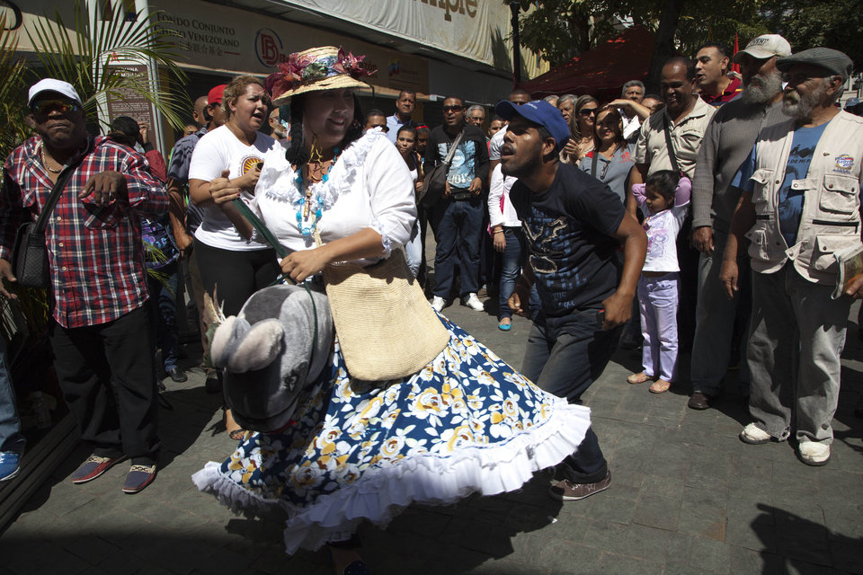 A bystander joins a performer in the traditional folk dance, La Burriquita, in Plaza Bolivar, a popular gathering place for supporters of President Hugo Chavez, in Caracas, Venezuela, Wednesday, Jan. 9, 2013. Venezuela\'s congress has voted to postpone the inauguration of Chavez, which was scheduled for Thursday, to let him recover from cancer surgery in Cuba. Critics say that violates the country\'s constitution. On Wednesday, Venezuela\'s Supreme Court backed the congress, ruling the Jan. 10th inauguration can be postponed. (AP Photo/Ariana Cubillos)