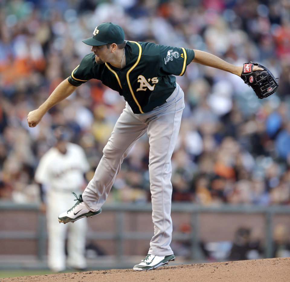 Photo - Oakland Athletics' Jason Hammel follows through on a pitch against the San Francisco Giants in the first inning of a baseball game Wednesday, July 9, 2014, in San Francisco. (AP Photo/Ben Margot)