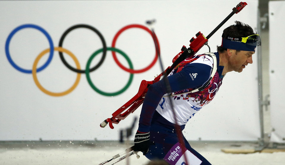 Photo - Norway's Ole Einar Bjoerndalen skis past the Olympic rings during the men's biathlon 12.5k pursuit, at the 2014 Winter Olympics, Monday, Feb. 10, 2014, in Krasnaya Polyana, Russia. (AP Photo/Lee Jin-man)